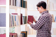 The young student looking for books in college library. Young student looking for books in college library Royalty Free Stock Photos