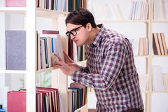 The young student looking for books in college library. Young student looking for books in college library Royalty Free Stock Image