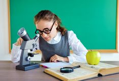 Young student looks through microscope, conducts research. stock photos