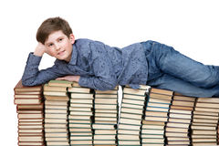 A young student lying on a stack of books Stock Photos