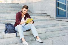 Young student making notes sitting on stairs. Young student sitting on stairs outdoors, making notes, preparing for exams at university or college. Education Stock Photos
