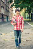 Young student man holding a book and tablet against a city. Background Royalty Free Stock Photos
