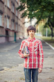Young student man holding a book and tablet against a city. Background Stock Photo