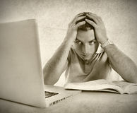 Young student man in stress overwhelmed studying exam with book and computer. Young student man worried frustrated and overwhelmed studying exam with book and Royalty Free Stock Images