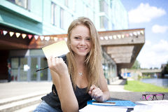 Young student outside with books showing sticky note Stock Images