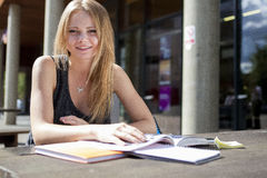 Young student outside reading book and smiling. Blond college girl sitting outside with books and notepad looking at camera smiling Royalty Free Stock Images