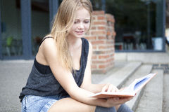 Young student outside reading book and smiling Stock Photos