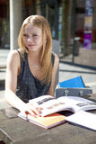 Young student outside reading books Royalty Free Stock Photo