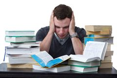 Young Student overwhelmed with studying. With piles of books in front of him Stock Photography