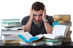Young Student overwhelmed with studying. With piles of books in front of him Stock Image