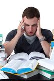 Young Student overwhelmed with studying. With piles of books in front of him Stock Photo