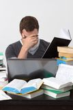 Young Student overwhelmed with studying. With piles of books in front of him Royalty Free Stock Images