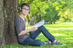 Young student in park listening to music on headphones Royalty Free Stock Image