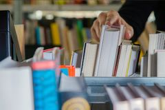 Young student picking a book from the shelf in the library. Preparing for exams, young man searching for or choosing a book in the. Public library in university royalty free stock image