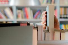 Young student picking a book from the shelf in the library. Preparing for exams, young man searching for or choosing a book in the. Public library in university royalty free stock photography
