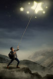 Young student pulling stars with rope. Concept of young student getting his ambition Royalty Free Stock Image