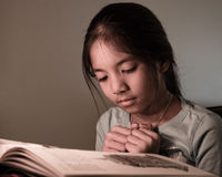 Young student reading a book. Young school girl reading a book, her face lit by candle light Royalty Free Stock Photos