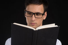 Young student reading book on black background. Stock Image