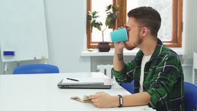 Young student is reading a book and drinking coffee. The guy is reading a book and page flipping. In breaks he drinks coffee from a plastic cup.  Young guy is stock video footage