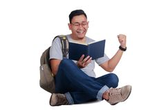 Young Student Reading Book, Happy Smiling Gesture. Attractive young Asian student reading book while sitting on the floor, isolated on white, success winning Stock Photography