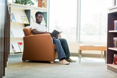 Young Student Reading Book In Library. Full length portrait of young African American student reading book in library Royalty Free Stock Image