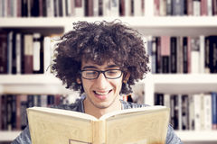 Young student reading  book in library Royalty Free Stock Photo