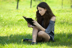 Young student reading book meadow Royalty Free Stock Images