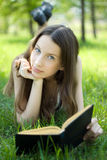 Young student reading book meadow Stock Image
