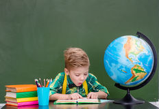 Young student reading a book near empty green chalkboard.  Stock Image