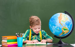 Young student reading a book near empty green chalkboard.  Stock Photos