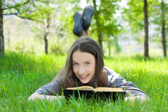 Young student reading book in park Stock Images