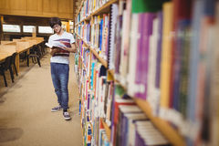 Young student reading book while standing near bookshelf Stock Photo