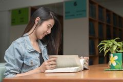 Young student reading book it in university library. Learning and education concept Stock Photography