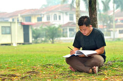 Young student reading books. Aon the green grass Royalty Free Stock Photo