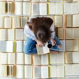 A young student reads a book and drinks coffee. Top view. Concept for World Book Day, lifestyle, study, education.  stock photo