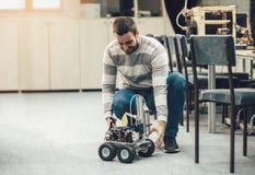 Young student of robotics preparing car robot for testing Stock Image
