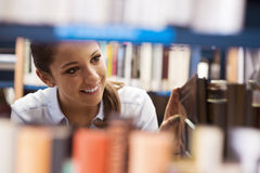 Young student searching for books. Young student at the library searching for books and peeking through bookshelves royalty free stock images