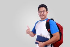 Young Student Showing Thumb Up Gesture OK Sign. Photo image portrait of funny attractive cute young Asian student in white shirt smiling and showing thumb up Royalty Free Stock Image