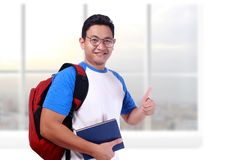 Young Student Showing Thumb Up Gesture OK Sign. Photo image portrait of funny attractive cute young Asian student in white shirt smiling and showing thumb up Stock Image