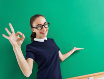Young student shows gesture okay and points to something. Photo of smiling teen near blackboard, education concept Stock Images