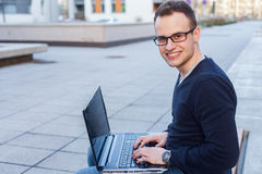 Young student sitting on a bench with laptop computer. Royalty Free Stock Images