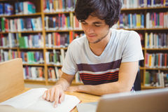 Young student sitting at desk reading a book Royalty Free Stock Photography