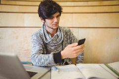 Young student sitting at desk and using mobile phone Stock Photo
