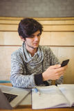 Young student sitting at desk and using mobile phone Royalty Free Stock Images