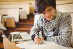 Young student sitting at a desk writing notes Stock Images
