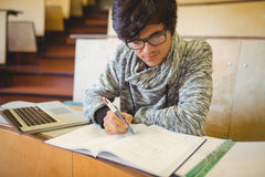 Young student sitting at a desk writing notes Stock Photos