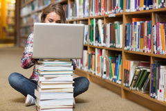 Young student sitting on library floor using laptop on pile of books Stock Photos