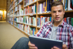 Young student sitting on library floor using tablet. In college Stock Photo