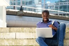Young student sitting outdoors and using laptop Royalty Free Stock Photos