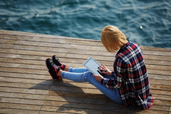 Young student is sitting on a pier near the ocean enjoying the beautiful weather and wrote its report Stock Image